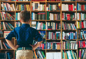 Child standing in front of shelves full of books