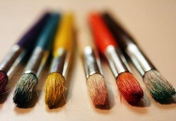 A row of colorful paintbrushes with paint on their bristles