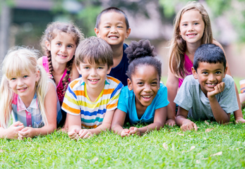 A group of young children laying on the grass outdoors
