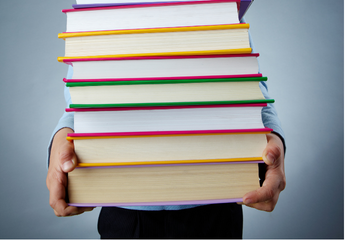 A person holding a big stack of books